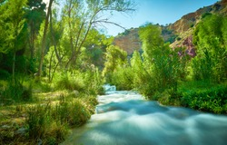 Beautiful long exposure landscape with a small river and the sun's rays on the trees and mountains in the background