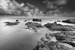 Beautiful long exposure .seascape rocky beach in black and white. soft and grain effect.