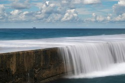 Beautiful long exposure seascape with waves of the Mediterranean Sea washing over a stone pier, gas processing platform in the background, and beautiful clouds; coast of Caesarea, Israel