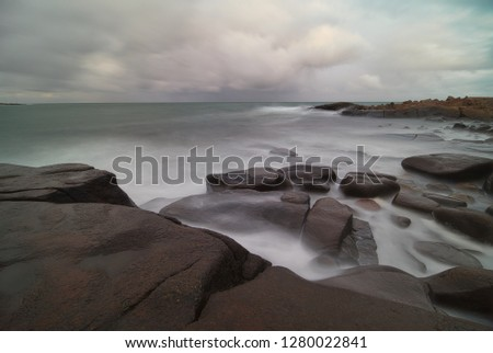 Beautiful long exposure view over Kattegatt along the Swedish coast outside Varberg by the Atlantic Ocean. Waves splashing against a rocky shore.