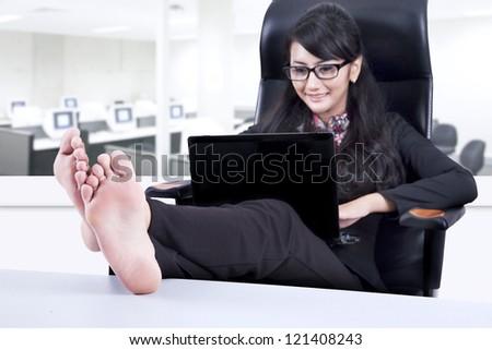 Beautiful long hair businesswoman put her legs up during office break