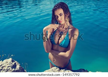 Beautiful long hair female model wearing bikini, posing in the water, outdoor portrait