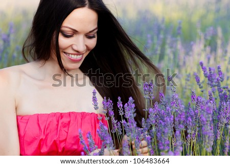 Beautiful long-haired brunette in a lavender field - stock photo