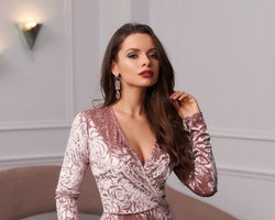 Beautiful long-haired brunette woman wearing pink velvet maxi dress and high heels standing against modern sofa on background. Stunning female model in evening outfit posing in room with white walls.