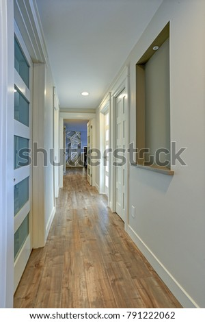 Beautiful Long Hallway Filled With White Doors Accented With Glass