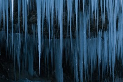 Beautiful long icicles of a frozen waterfall, with water flowing and crashing down and Ice water dripping from the tips of icicles in a cold eery and moody atmosphere in a cave in the mountains