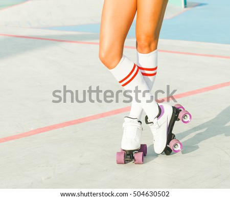 Beautiful long-legged girl posing on a vintage roller skates in denim shorts and white T-shirt in the skate park on a warm summer evening. Part of body. Rollers quads derby.