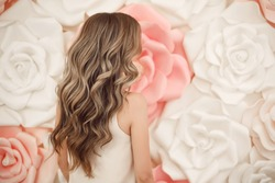 Beautiful long wavy hair style. Bride wedding hairstyle over flowers copyspace. Beauty hairdressing salon.