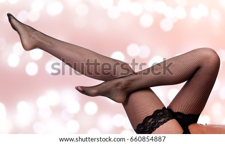 Beautiful long woman's legs in black net pantyhose on an abstract background with blurred lights