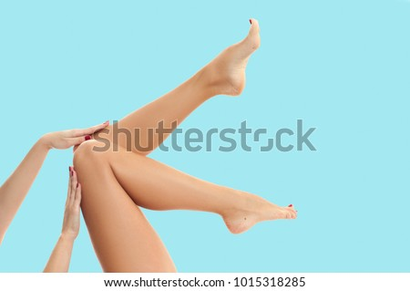 Beautiful long woman's legs with smooth skin after depilation on pastel blue background.