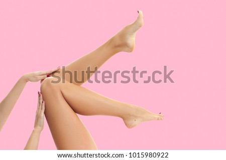 Beautiful long woman's legs with smooth skin after depilation on pastel pink background.