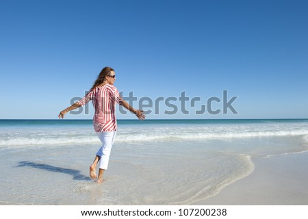 Beautiful looking mature woman, happy and friendly at beach, enjoying retirement, isolated with ocean and blue sky as background and copy space.
