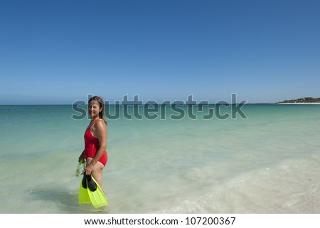 Beautiful looking mature woman in red bathers and yellow snorkel gear, swimming in shallow water of tropical beach, isolated with ocean and blue sky as background and copy space.