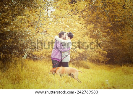 beautiful love couple man and woman on walk with dog in autumn nature
