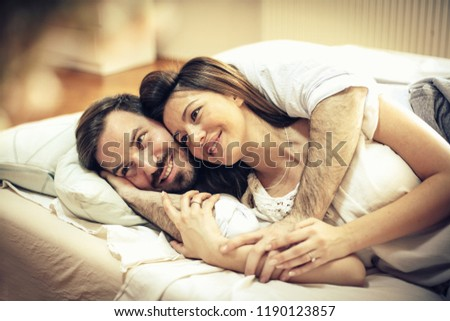 Beautiful love. Happy young couple in bed. Space for copy.