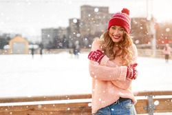 Beautiful lovely middle-aged girl curly hair warm peach sweater red knitted hat glove stands ice rink background Town Square Christmas mood lifestyle Happy holiday woman  snowy day Winter leisure