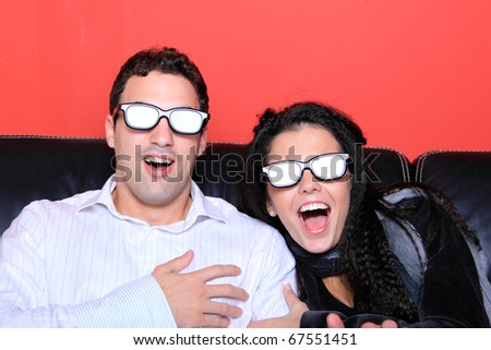 Beautiful loving couple at home watching a 3D movie