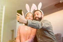Beautiful loving couple making selfie on smartphone with pink rabbit ears on head. Sel isolation and covid19 quarantine