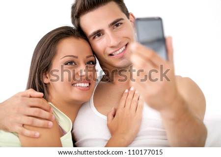 Beautiful loving couple photographing themselves by mobile phone, smiling