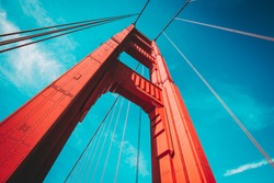 Beautiful low angle view of famous Golden Gate Bridge with blue sky and clouds on a sunny day in summer with retro vintage post crocessing filter effect, San Francisco Bay Area, California, USA