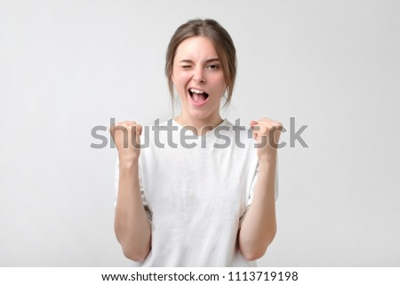Beautiful lucky european girl feeling excited and happy after she won lottery unexpectedly or passing diffficult exam in college, keeping mouth opened and fists up