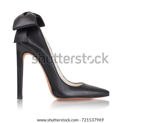 Beautiful luxurious elegant elegant female black leather shoe decoration with bow on high heel on a white background, side view #721537969