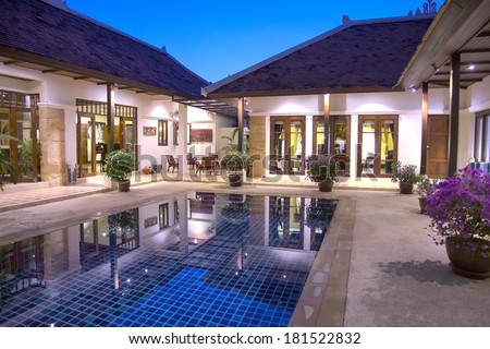 Beautiful, luxury, Balinese style  holiday villa in Phuket, Thailand lit up and reflected in the swimming pool taken early evening during the blue hour.. Image by Kevin Hellon.