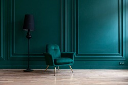 Beautiful luxury classic blue green clean interior room in classic style with green soft armchair. Vintage antique blue-green chair standing beside emerald wall. Minimalist home design