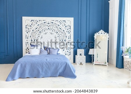 Beautiful luxury classic clean interior bedroom in white and deep blue color with king-size bed and chic carved furniture. Bright modern stylish interior bedroom and living room in minimalist style