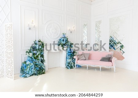 Beautiful luxury classic clean interior living room in white color with pink sofa fireplace flower composition. Bright modern stylish interior living room with furniture in classic minimalist style