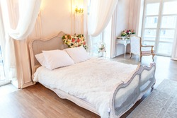 Beautiful luxury classic white bright clean interior bedroom in baroque style with king-size bed, large window, armchair and flower composition