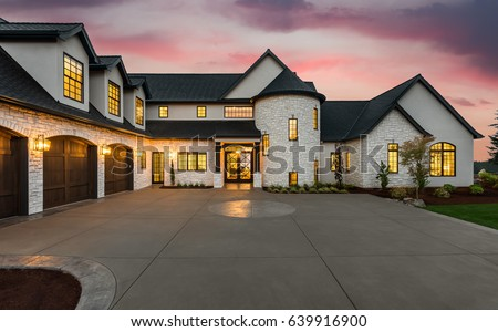 Beautiful Luxury Home Exterior at Twilight with Colorful Sunset Sky