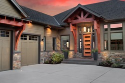 Beautiful Luxury Home Exterior Detail at Sunset: Garage Door with Wood Beams and Colorful Sunset Backdrop