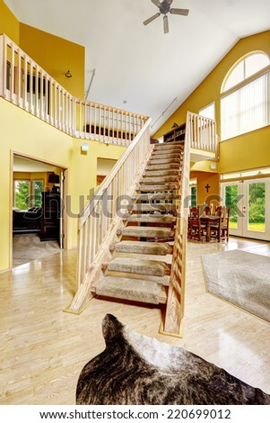 Beautiful luxury house with high vaulted ceiling and loft with wooden staircase. Animal skin rug decorate the hardwood floor