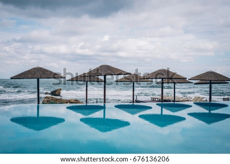 Beautiful luxury outdoor pool view with beach tiki hut and view to the sea, Crete Island, Greece #676136206