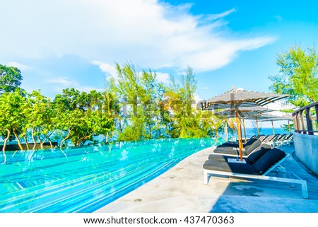 Beautiful luxury outdoor swimming pool in hotel resort with umbrella and chair on blue sky neary sea and ocean - Holiday vacation concept for background #437470363