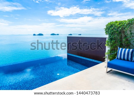 Beautiful luxury outdoor swimming pool with sea ocean view on blue sky white cloud around pillow on sofa decoration for holiday vacation and travel #1440473783