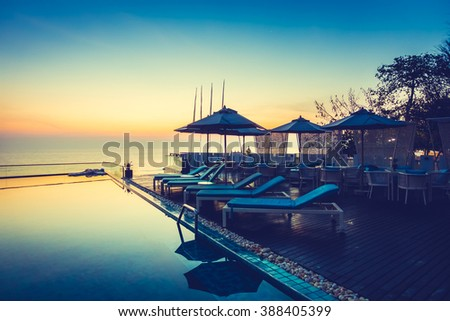 Beautiful luxury swimming pool in hotel resort with silhouette umbrella and chair around pool with sunset and twilight times - Vintage Filter and Boost up color Processing