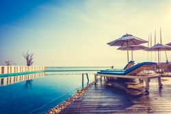 Beautiful luxury swimming pool in hotel resort with umbrella and chair in sunset times - Vintage Filter and Boost up color processing