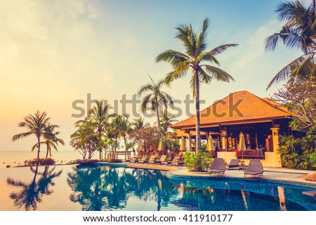Beautiful luxury Swimming pool with palm tree and sea background in hotel pool resort - Vintage Filter and Boost up color Processing