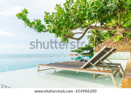 Beautiful luxury umbrella and chair around outdoor swimming pool in hotel and resort - boost up color processing #654986200