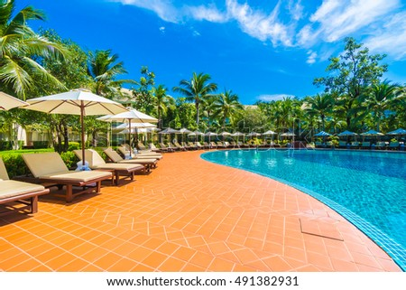 Beautiful luxury umbrella and chair around outdoor swimming pool in hotel and resort with coconut palm tree on blue sky - Boost up color Processing #491382931