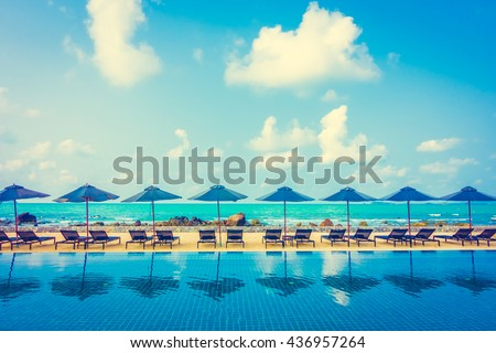 Beautiful luxury umbrella and chair around outdoor swimming pool in hotel resort neary sea and beach - Vintage Filter