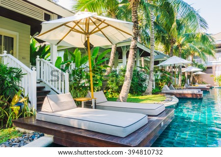 Beautiful luxury Umbrella and chair around swimming pool in hotel pool resort - Vintage Light Filter #394810732