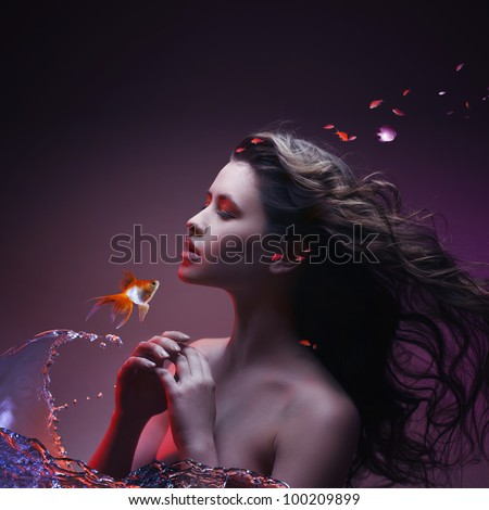 Beautiful magic girl talking with golden fish that made water splashes