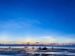 Beautiful, magical sunset, sunrise. Calm sea with boats on the background sky and clouds. Low tide on beach. Blue trend