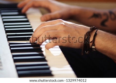 Beautiful male hands, on which bracelet and tattoo, play on musical modern synthesizer #1329974012