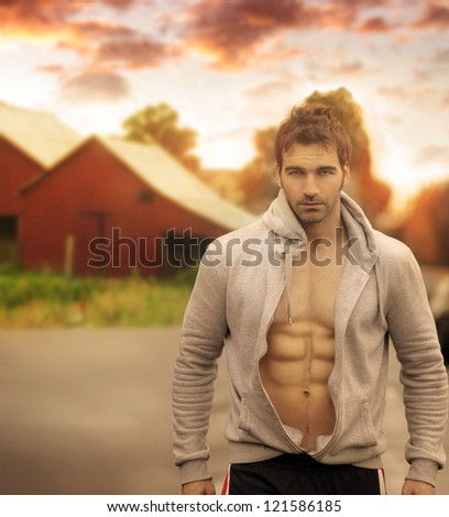 Beautiful male model with great body in romantic rustic outdoor setting with red barn in background and moody sky above #121586185