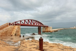 Beautiful Malta sea shore pier view with red bridge on rainy cloudy day with big white waves , yellow sandstone rocks, shrubs, blue water, and skies. white fence, water