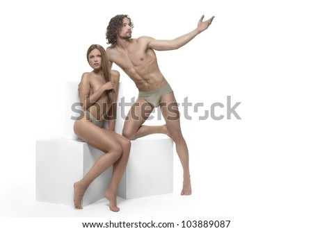 beautiful man and woman Adam and Eve, posing on a white background with white cubes